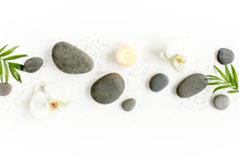 Spa Stones, Palm Leaves, Flower White Orchid, Candle And Zen Like Grey Stones On White Background. Flat Lay, Top View