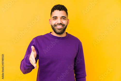 Young mixed race arabic man isolated stretching hand at camera in greeting gesture Fototapete