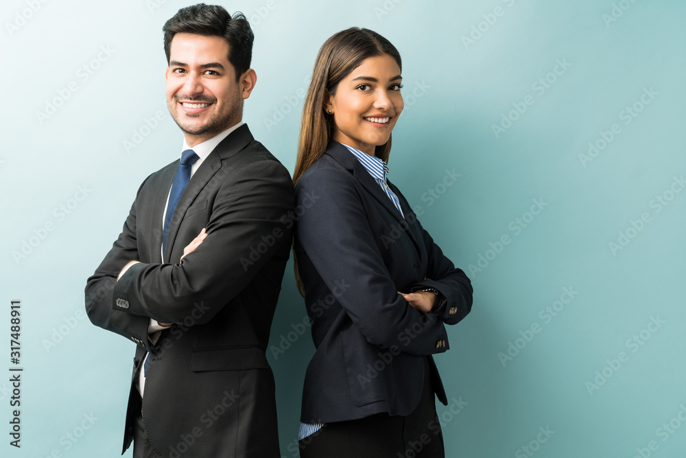 Fototapeta Business Colleagues Standing With Arms Crossed In Studio
