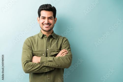 Obraz Confident Smiling Man Standing In Studio - fototapety do salonu