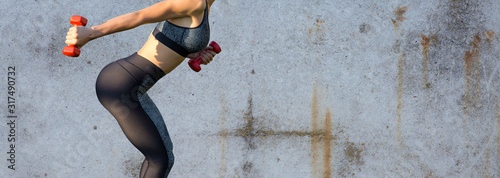 Photo A sporty slim girl in leggings and a top is standing against a concrete wall and performs a set of exercises with dumbbells
