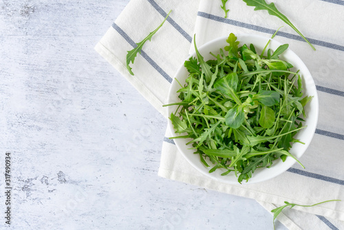 Fresh green arugula leaves in a plate on a gray background, top view, copy space Canvas Print