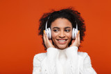 Cheerful young african woman listening to music
