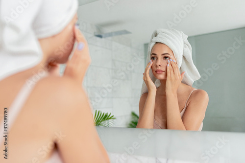 Photo Young woman applying anti-wrinkle eye cream standing behind mirror in home bathroom