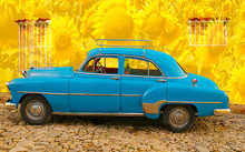 Blue Almendron Parked On Yellow Wall With Sunflowers, Cuba