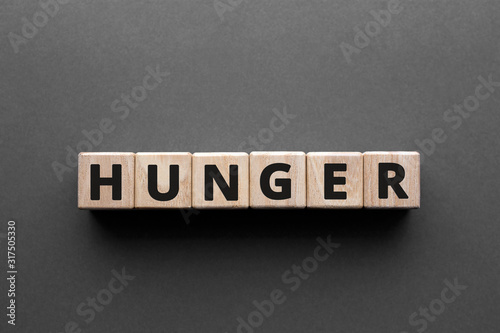 Fotografiet Hunger - words from wooden blocks with letters, need to eat hunger concept, top