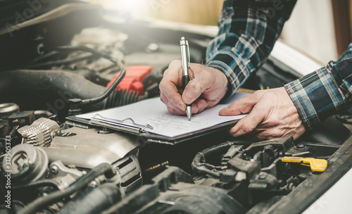 Car mechanic checking a car engine Canvas Print