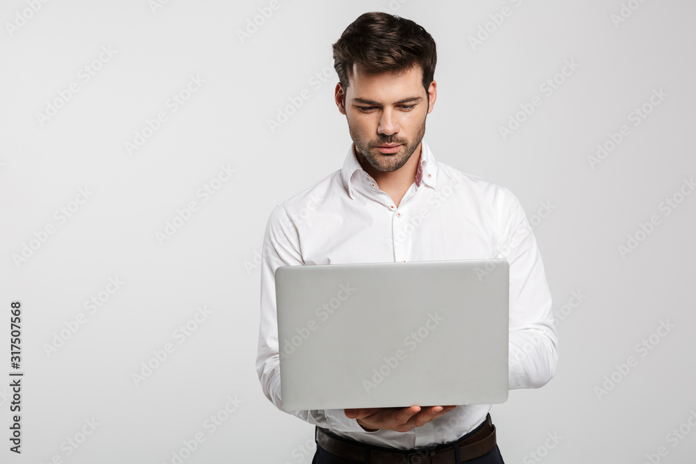 Fototapeta Image of young successful businessman holding and using laptop