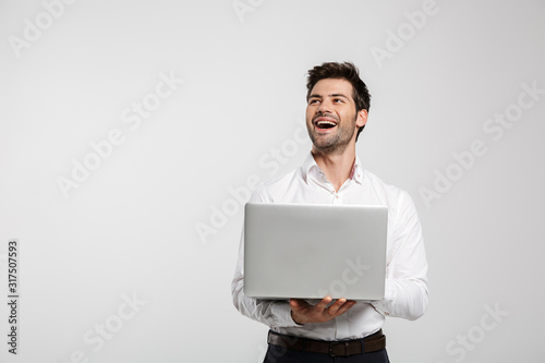 Obraz Image of young laughing businessman holding and using laptop - fototapety do salonu