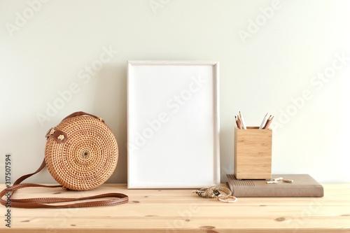 White blank frame mockup for poster or photo on wooden shelf, round rattan bag, boho style bracelets Wallpaper Mural