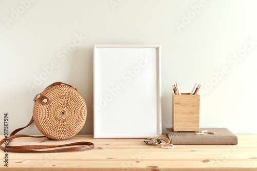 Photo White blank frame mockup for poster or photo on wooden shelf, round rattan bag, boho style bracelets