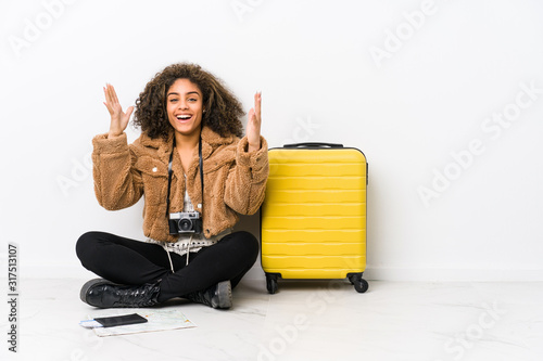 Photo Young african american woman ready for a travel receiving a pleasant surprise, excited and raising hands