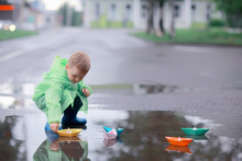 A Boy Plays Boats In A Puddle ...