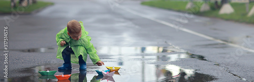 a boy plays boats in a puddle / childhood, walk, autumn game in the park, a chil Wallpaper Mural