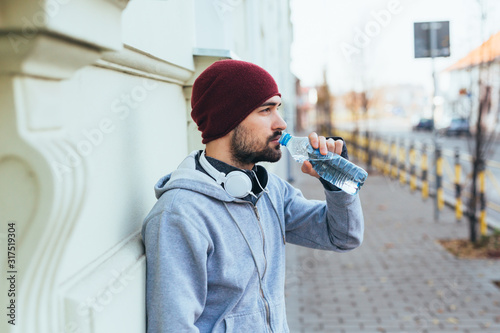Fototapeta handsome young man jogging outdoors. drinking water