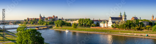 Krakow, Poland. Wide aerial panorama with Vistula river, Wawel cathedral and castle, Skalka church and Paulinite monastery, bridge, parks and promenades along the riverside. Summer, sunset light