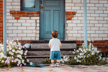 Back View Of Cute Lonely Little Boy Standing Outside In Front Of Blue Closed Door Of Old House. Loneliness. Abandoned Child Waiting For Mother.