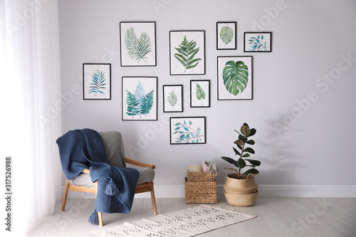 Fototapeta Beautiful paintings of tropical leaves on white wall in living room interior obraz