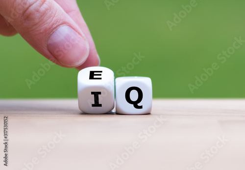 Photo Hand turns a dice and changes the expression IQ (Intelligence Quotient) to EQ (Emotional Intelligence/Quotient)