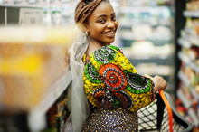 Happy African Woman In Traditional Clothes And Veil Looking Product At Grocery Store, Shopping In Supermarket.  Afro Black Women Costumer With Basket Buying Food At The Market.