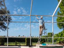 Handyman On Ladder Cleaning Outdoor Pool Cage Enclosure. Screened Swimming Pool Lanai Maintenance And Screen Repair.