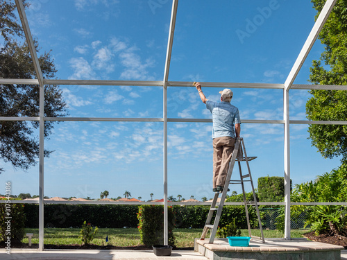 Handyman on ladder cleaning outdoor pool cage enclosure Canvas Print