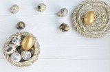 Easter.  quail eggs and one golden colored egg in a straw bowl on a white wooden background with space for text
