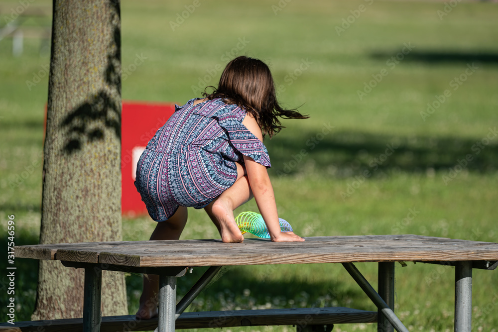 Fototapeta unknown little girl plays with her slinky on a picnic table