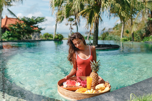 Photo Pretty smiling young woman in red swimsuit  is preparing to eat breakfast in the swimming pool