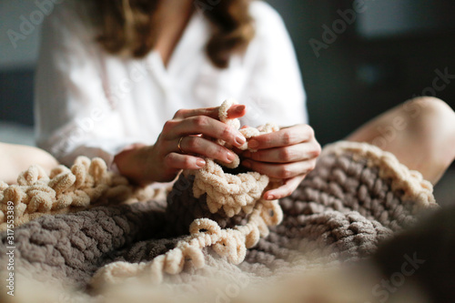Caucasian woman knits large toy rug with hands