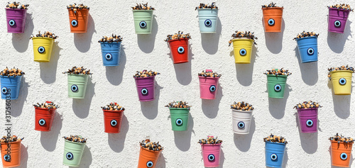 Valokuvatapetti small decorative colorful buckets with eyes on wall