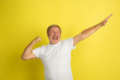 Successful winner's gesture. Caucasian man portrait isolated on yellow studio background. Beautiful male model in white shirt posing. Concept of human emotions, facial expression, sales, ad. Copyspace