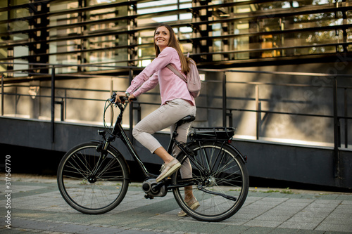 Young woman riding e bike in urban enviroment Canvas