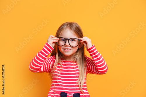 Fototapeta Portrait of young smiling girl wearing glasses on yellow background obraz