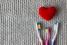 Three Toothbrushes And A Red Heart On A Knitted Gray Background. Two Adults, One Children's Toothbrush And Heart. Love, Family Concept And Valentines Day, Family With A Child. Copy Space