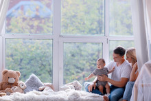 Mom Dad And Baby Little Toddler Sitting On The Window / Young Family In A New Apartment, Beautiful Housing