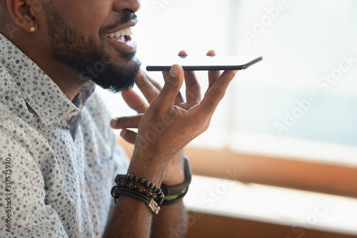 Photo Closeup view african guy talking with friend on speakerphone
