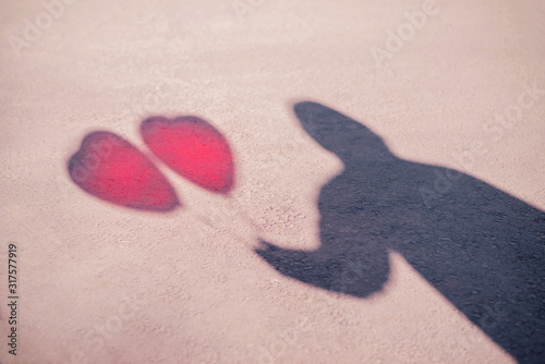 Shadow of male figure with two red balloons shaped like heart Canvas Print