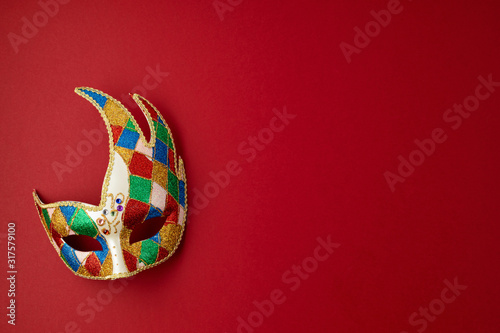 Festive, colorful mardi gras or carnivale mask and accessories over red background Fototapete