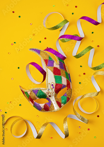 Obraz na plátne Festive, colorful mardi gras or carnivale mask and accessories over yellow background