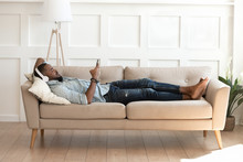 African Man In Headphones Lying Resting On Couch With Smartphone
