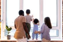 Happy Ethnic Family With Two Children Looking Out The Window Standing In The Apartment