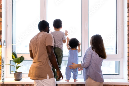 Fotomural Happy ethnic family with two children looking out the window standing in the apa