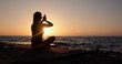 A woman in a lotus position with her hands up sits on the seashore awaiting for the appearance of the sun.