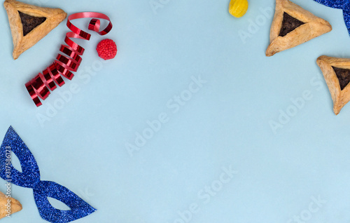 Triangular cookies with poppy seeds ( hamantasch or aman ears ), candy, glitter mask, serpentine for jewish holiday of purim celebration on blue background with space for text Canvas Print