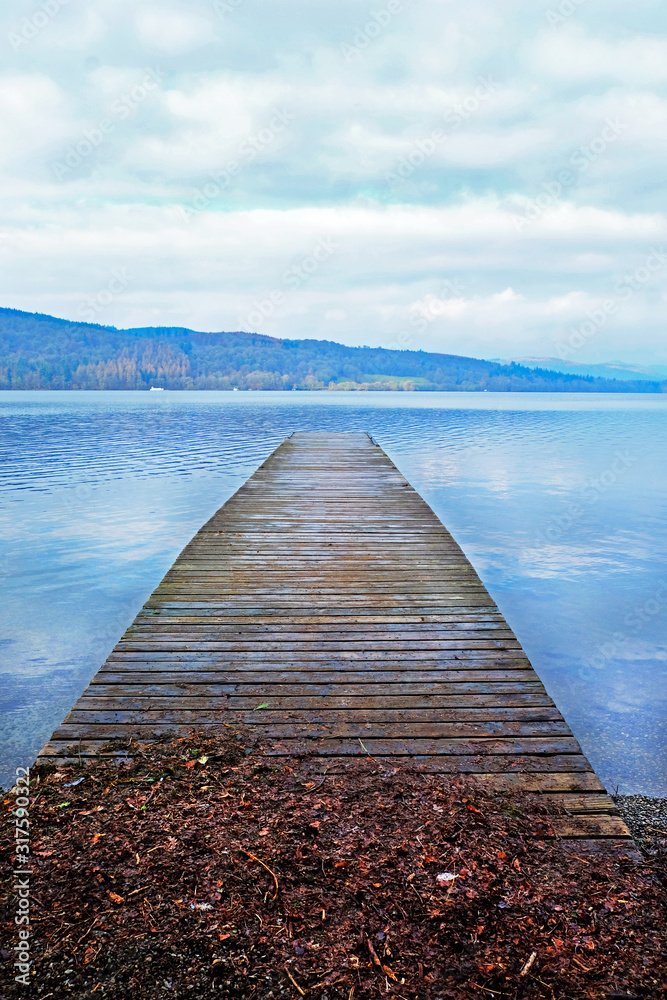 Fototapeta A long wooden jetty on a lake, looking out over a straight out over a clear calm blue lake