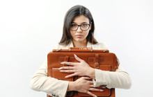 Portrait Of A Clinging Mixed Race Woman In Eyeglasses Embracing Brown Leather Handbag, Isolated White Background