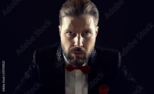 Portrait of brutal bearded male wearing black suit, red bowtie, and rose looking Fototapet