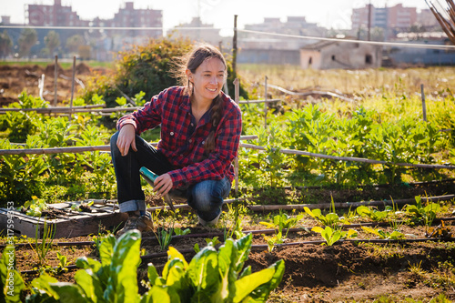 Young woman gardening in urban garden Fototapeta