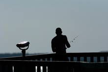 Silhouette Of Man Fishing At D...